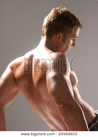 Shaped and young man stretching his muscles.