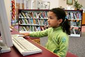 stock photo of storytime  - Child in a school library in the computer - JPG