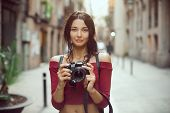 Attractive Tourist Woman Photographer With Dslr Camera Looking At Camera Outdoor In City Street In B poster