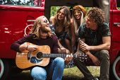 Group of young hippies men and women laughing and playing guitar near vintage minivan into the natur poster