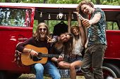Group of joyous hippies happy men and women laughing and playing guitar near vintage minivan into th poster