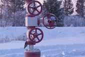 Gas Or Oil Valve Covered With Snow. Oil Pump Jack In Work. Latch On A Oil Well poster