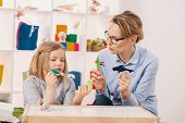 Mother With Toys Playing With Daughter With Aspergers Syndrome At Home poster
