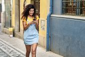 Young African Girl Walking On The Street Looking At Her Smart Phone. Smiling Arab Woman In Casual Cl poster