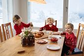 Kids Having Breakfast On Christmas Morning. Family Eating Bread And Drinking Milk At Home On Snowy W poster