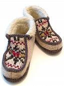 stock photo of budge  - The budge hand made knitted slipperswith ornate - JPG