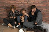 Poor Homeless Family Sitting On Floor Near Brick Wall poster