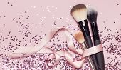 Different Cosmetic Makeup Brushes With Pink Ribbon And Holographic Glitter Confetti In The Form Of S poster