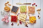 Assortment of healthy fresh breakfast toasts. Bread slices with peanut butter and various fruits and poster