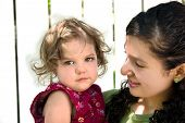 stock photo of babysitting  - a young latino girl holding a toddler