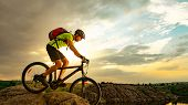 Cyclist Riding the Bike on the Rocky Trail at Sunset. Extreme Sport and Enduro Biking Concept. poster