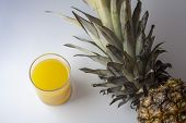 Single Pineapple, Ananas With A Glass Of Juice Isolated On White Background, Negative, Copyspace. To poster