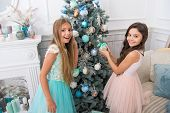 Sisters Decorating Tree. Cherished Holiday Activity. Kids Fashionable Dresses Decorating Christmas T poster