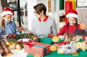 Young mother showing small packed giftbox to one of her little daughters during xmas preparations poster