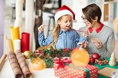 Cheerful little girl in xmas cap and her mother discussing what to put into small giftbox poster