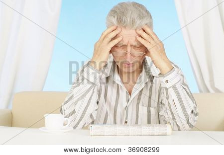 Elderly man is reading the newspaper