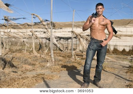 Muscled Man Shirtless Wiith Jeans In Desolated Landscape