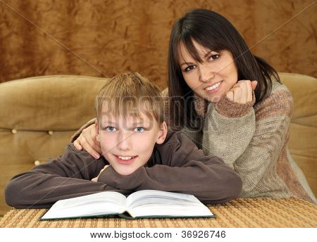 Beautiful happy Caucasian mother with her son reading a book