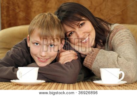 Beautiful mama and son sitting on the couch with a cup