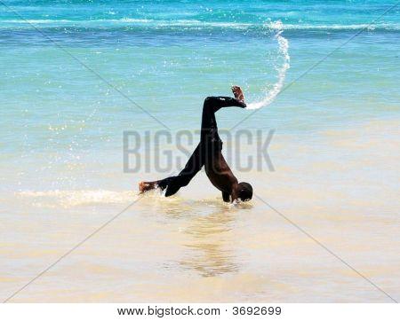 Boy Doing Cartwheels On The Beach