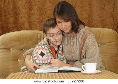 A beautiful happy mother with her son sitting on the couch