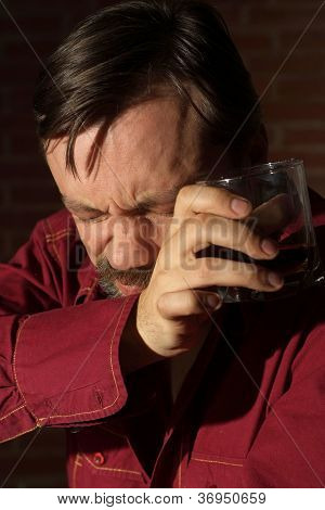 Drinking man in a red shirt