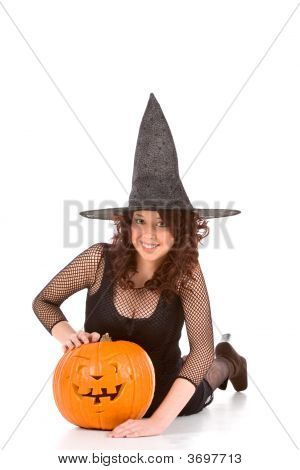 Teen Girl In Halloween Hat With Carved Pumpkin  (Focus On Pumpkin)