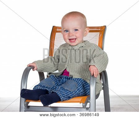 Happy Smiling Baby In A Highchair