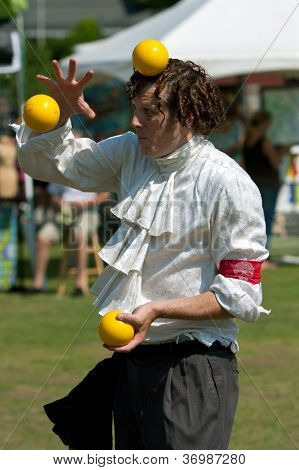 Juggler Balances Ball On Head While Performing At Festival
