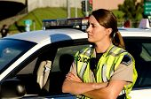 stock photo of lightbar  - a female police officer crosses her arms as she stands next to her patrol car - JPG