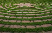 stock photo of stroll  - Circular outdoor prayer labyrinth made of bricks and green grass - JPG