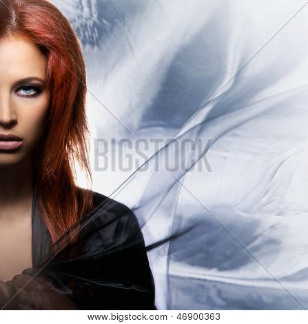 Portrait of beautiful woman over the blowing silk background