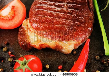meat entree : grilled beef steak served with hot cayenne peppers red tomato green chives on metal pan isolated over white background