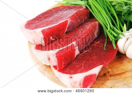 raw meat : fresh beef pork fillet pieces with garlic and green stuff on wood isolated over white background