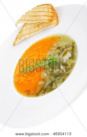 european cuisine: dual components vegetable soup served with toasts over white ceramic dish