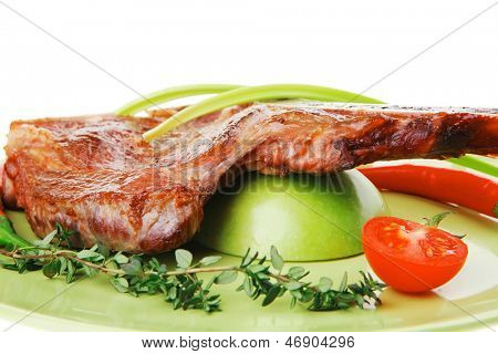 savory : grilled spare rib on green dish with thyme pepper and tomato isolated over white background