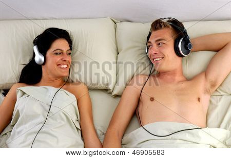 Young couple listening music to headphones on bed.