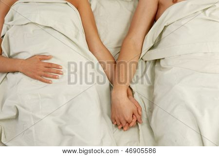 Lovely couple lying down on bed and shaking hands.