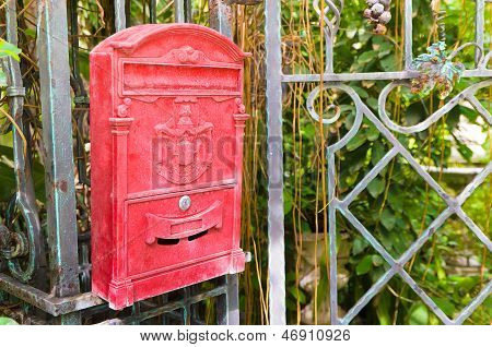 Traditional old English red postbox hang on gate