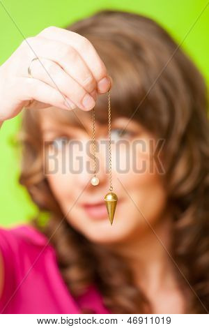 Beautiful woman with pendulum in her hand, tool for dowsing.