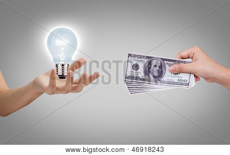 Hand with dollars and light bulb