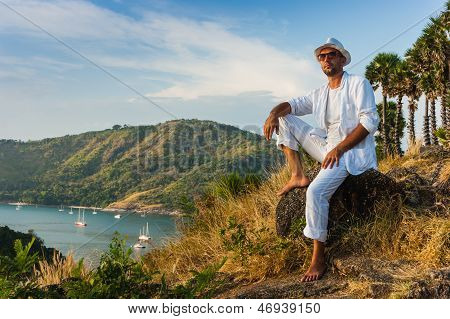The Man  In A White Suit And Hat Sitting On A Rock On The Sea Background