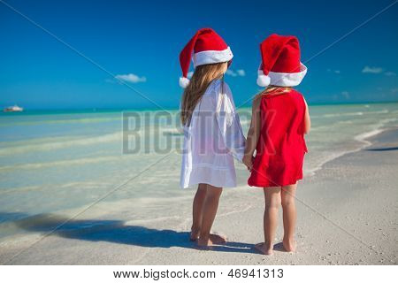 Two Little Cute Girls�in Christmas Hats Have Fun On The Exotic Beach