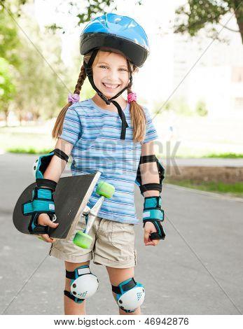 cute little girl in a helmet holding a skate