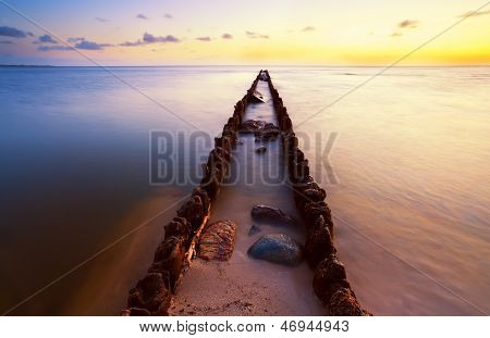 Long Wooden Dike In North Sea At Sunset