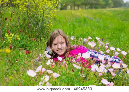 Happy relaxed kid girl smiling on a spring flowers meadow with green grass