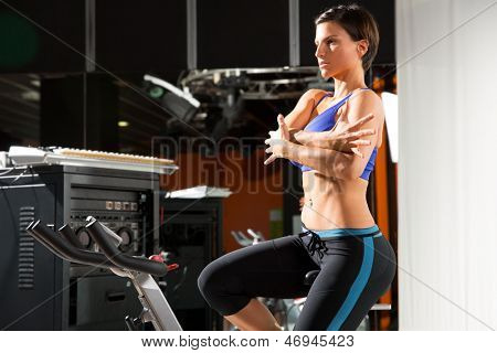 Aerobics monitor trainer woman stretching exercises after workout at gym
