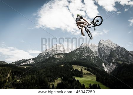 biker jumps high in front of mountains