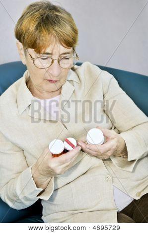 Elderly Woman Reading Pill Bottles