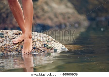 Woman on rock at beach dipping toes in water, having fun outdoor lifestyle